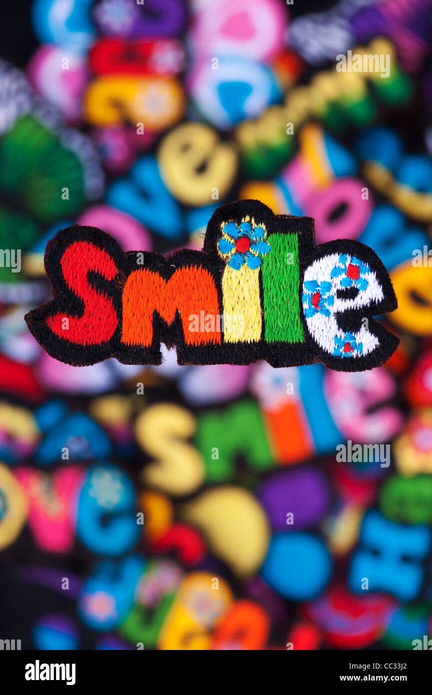 Embroidery iron on patches of Multicoloured Smile, Love, Peace, Happy, and Groovy words on a black background - Stock Image