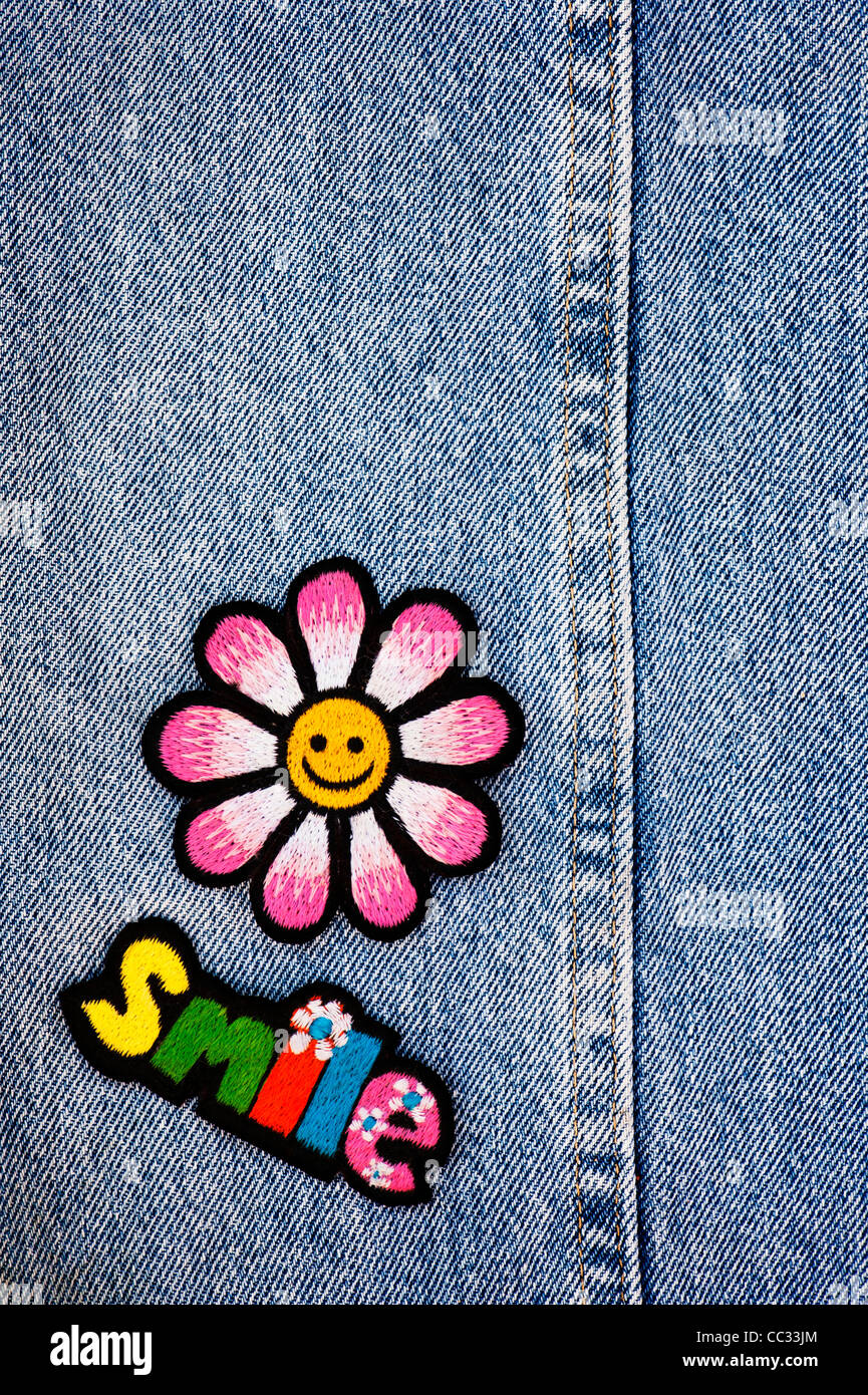 Embroidery iron on patches of Multicoloured Smile word with a smiley face flower on a denim jean background - Stock Image