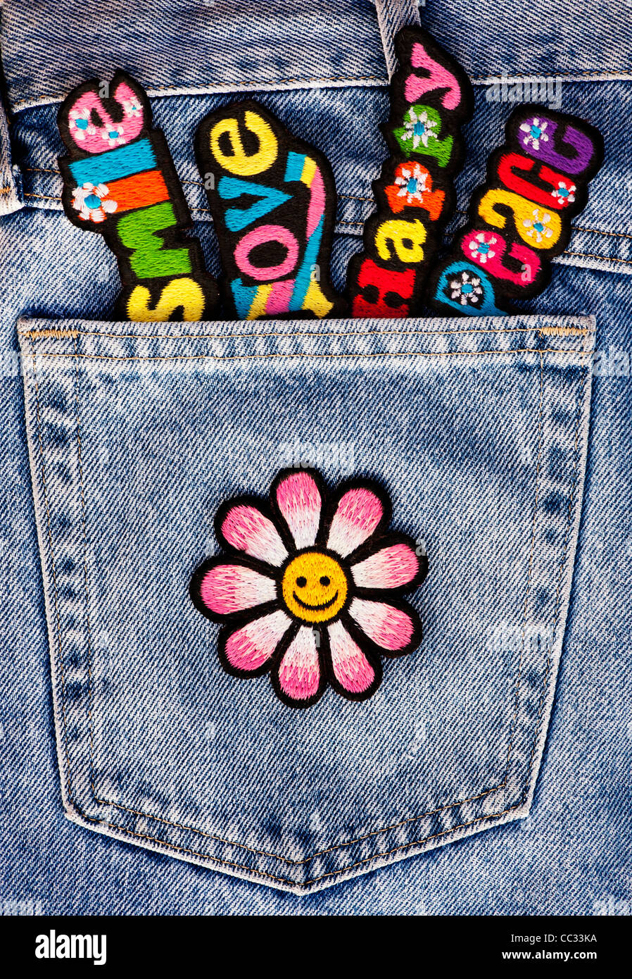 Embroidery iron on patches of Multicoloured Love, Peace, Happy words with a smiley face flower in a denim pocket - Stock Image