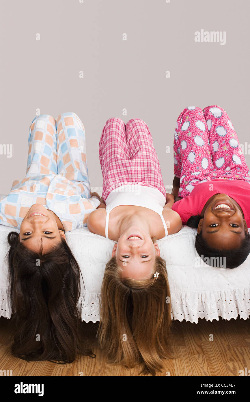 USA, California, Los Angeles, Portrait of three girls (10-11) lying on bed with heads down - Stock Image