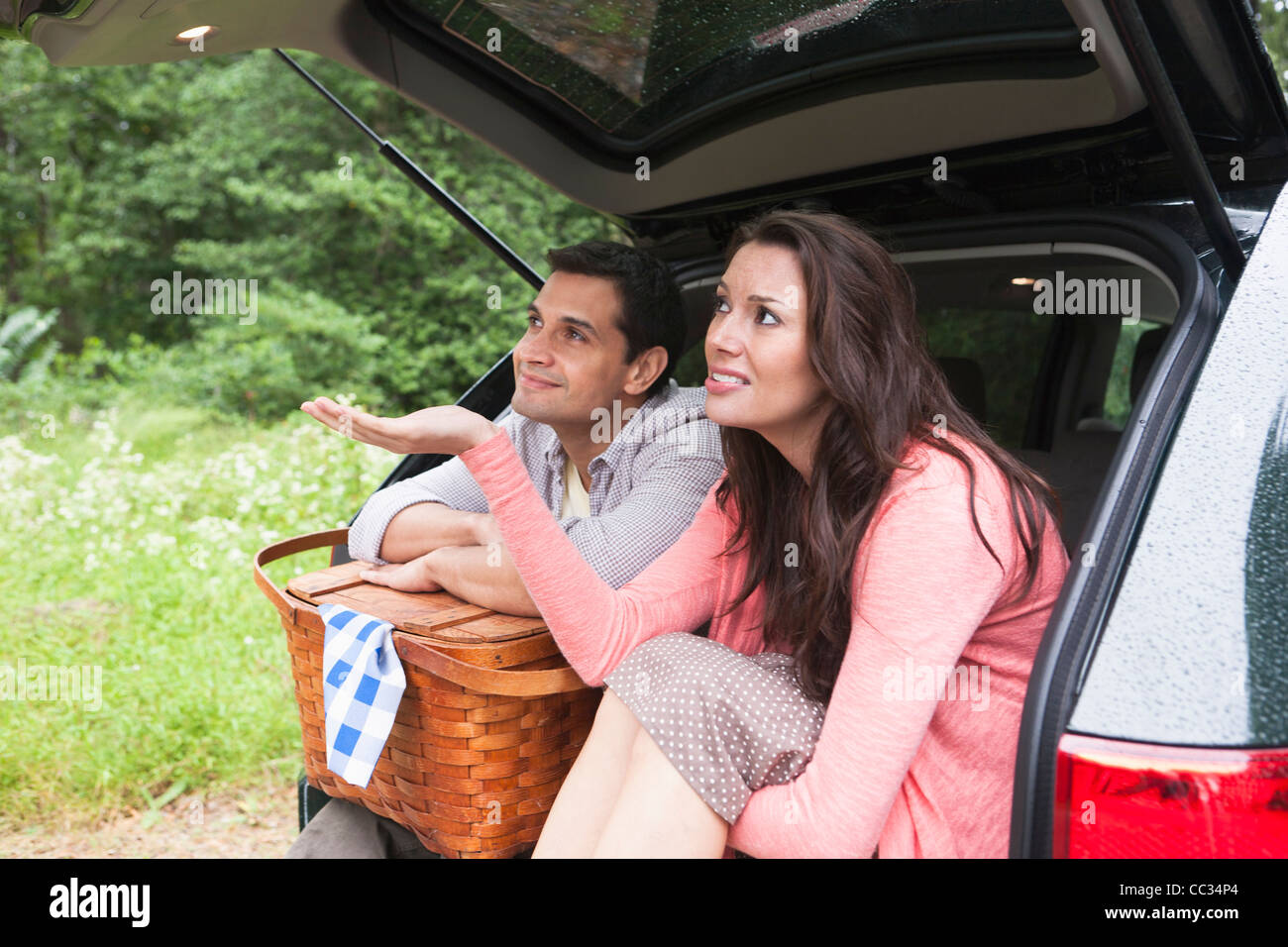 USA, New Jersey, Couple with picnic basket sitting in car trunk - Stock Image
