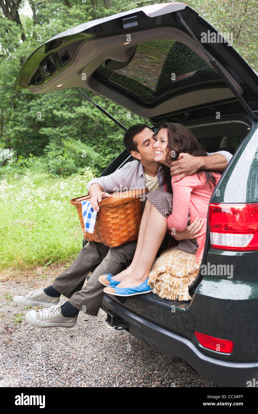 USA, New Jersey, Happy couple with picnic basket sitting in car trunk - Stock Image