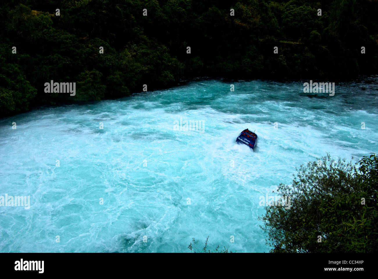 Jet boat tour turbulent whirling frothy currents of Waikato River below Huka Falls - Stock Image