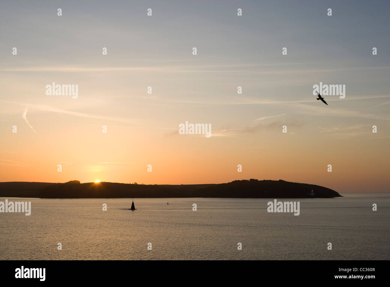 The sun rises over St Anthony's Head, Roseland peninsula, Cornwall seen from Pendennis Point. - Stock Image