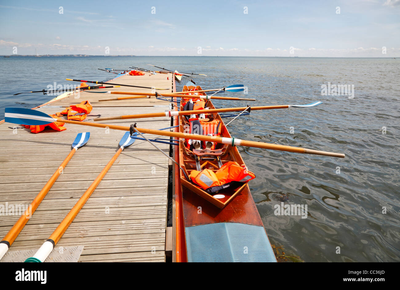 Single-scullers and coxless four at the pontoon jetty for a lunch break during a youth activity week in Rungsted - Stock Image