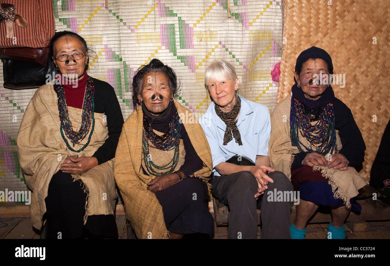 India, Arunachal Pradesh, Ziro Valley, Mida, group of older tattooed Apatani women with western visitor - Stock Image