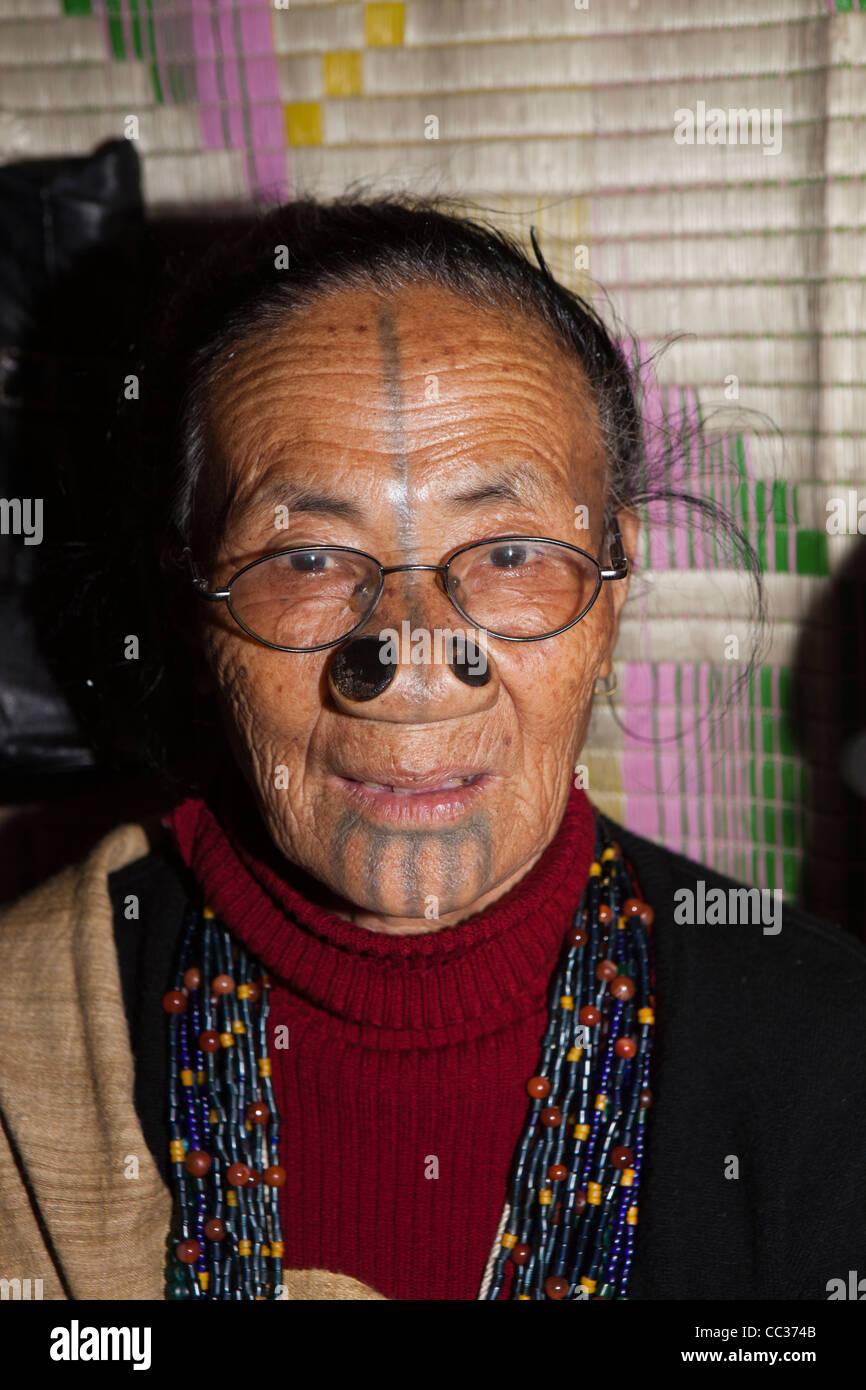 India, Arunachal Pradesh, Ziro Valley, Mida, face of older tattooed Apatani woman with facial tattoos and nose plugs - Stock Image