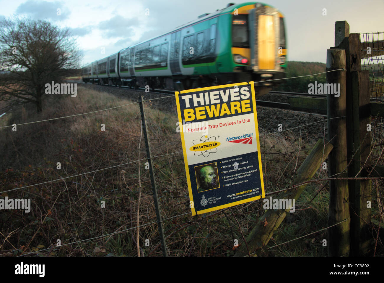 Sign by a railway line which warns against theft of metals as there are forensic tracking devices - Stock Image