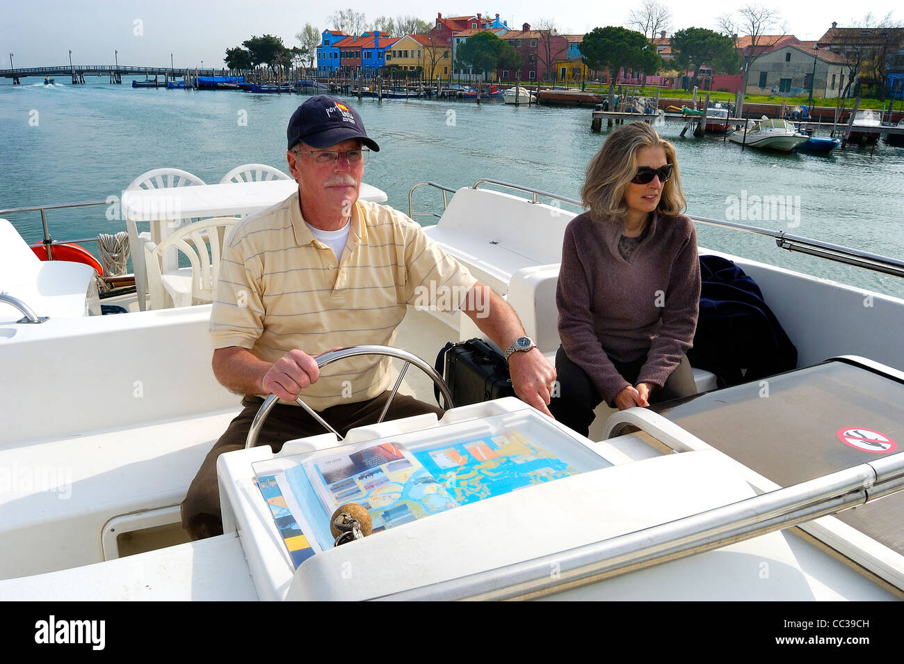 Skipper and crew driving a 40 ft charter motor boat past the island of Burano, Venice, Italy - Stock Image
