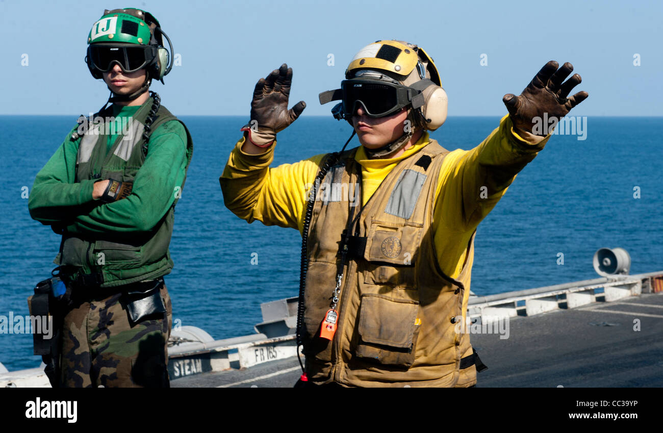 Directing aircraft onto catapult four on the flight deck of the Nimitz-class aircraft carrier USS John C. Stennis Stock Photo