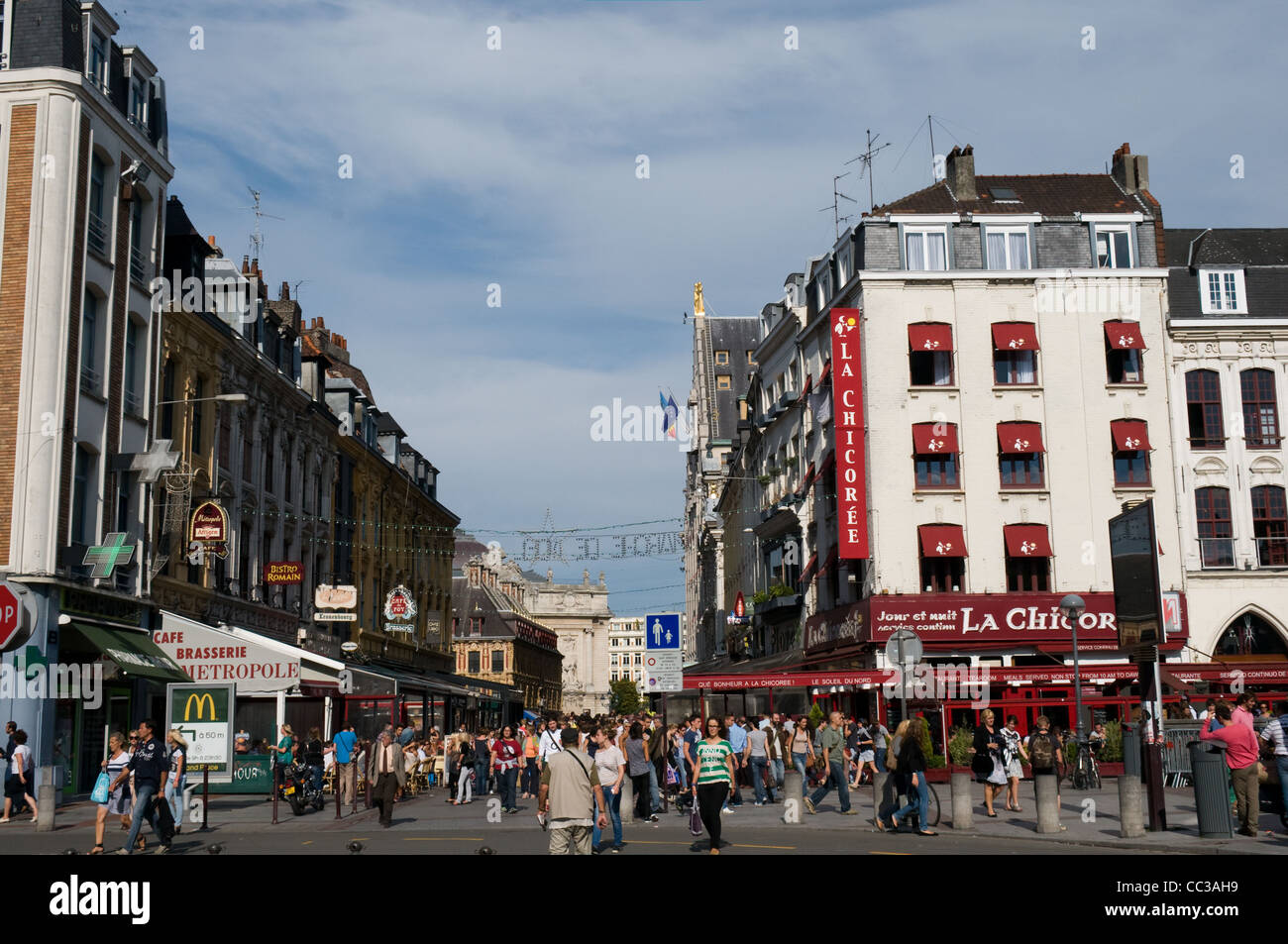 Tourists and locals enjoy a sunny day in Lille, France. The cafes and resturants in Pl. Rihour are doing a good - Stock Image
