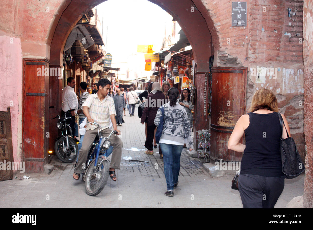 Marrakech alley way in the Medina with pedestrians and cyclists - Stock Image