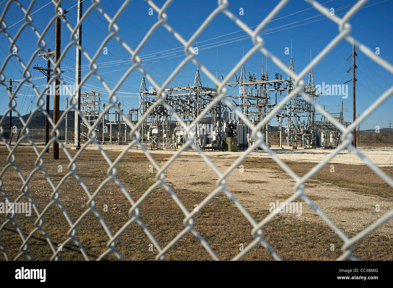 Electricity transformation station behind fence - Stock Image