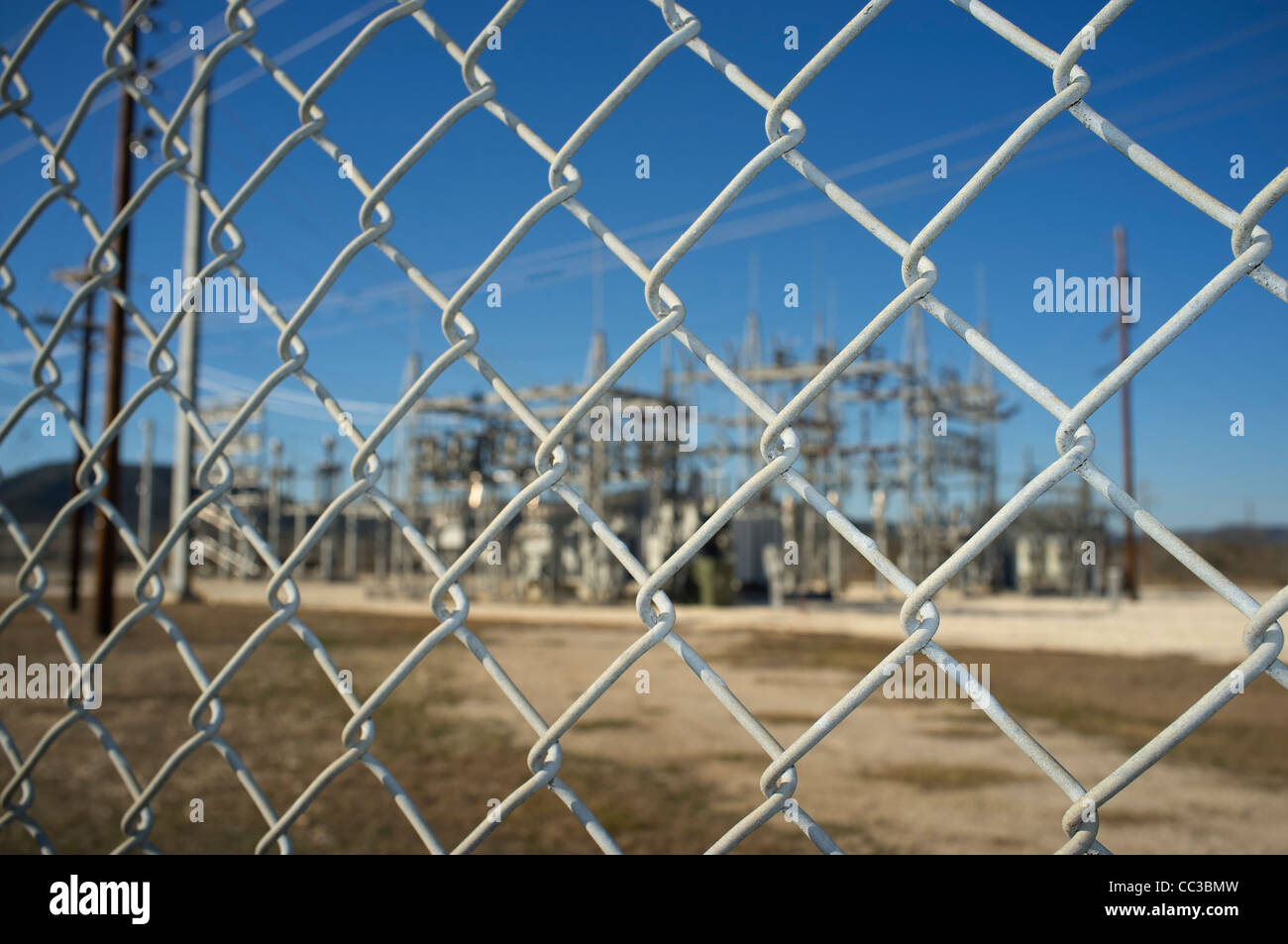 Chain-link fence restricting access to power transformation and distribution station in Texas, USA - Stock Image