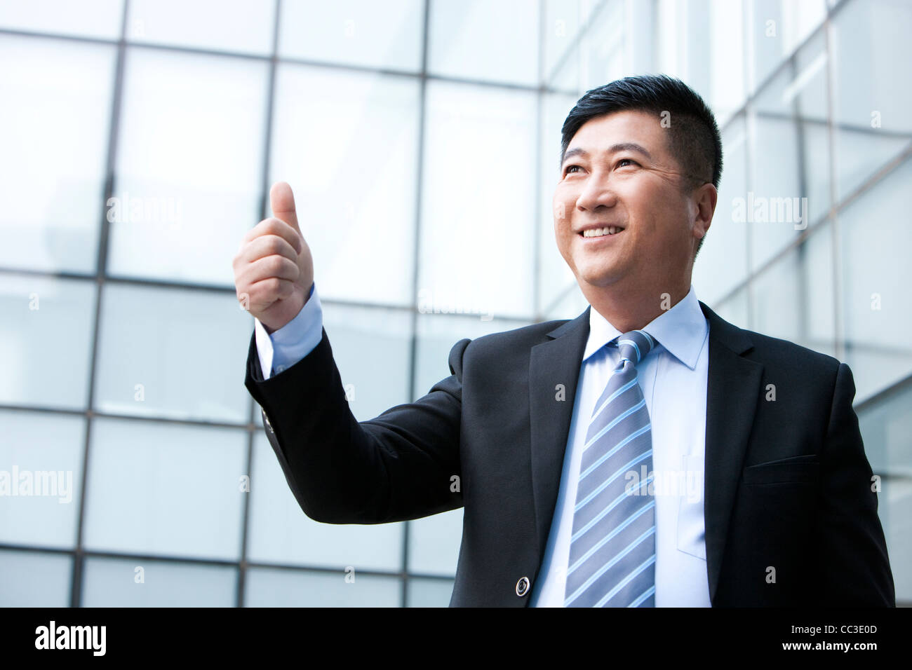 Businessman giving the thumbs-up sign - Stock Image
