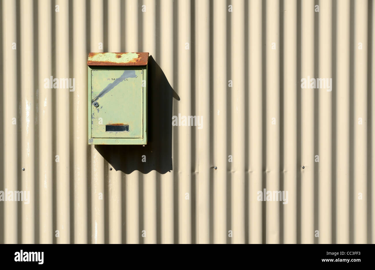 Single French Metal Letter Box Post Box or Mail Box on Corrugated Iron Wall - Stock Image