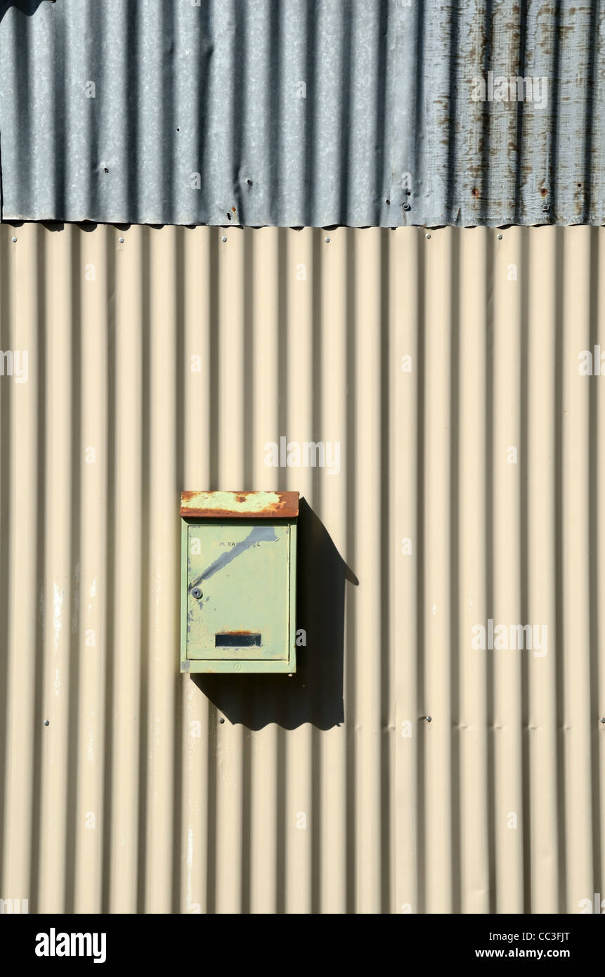 French Letter Box Post Box or Mail Box Fixed to a Corrugated Iron Wall - Stock Image