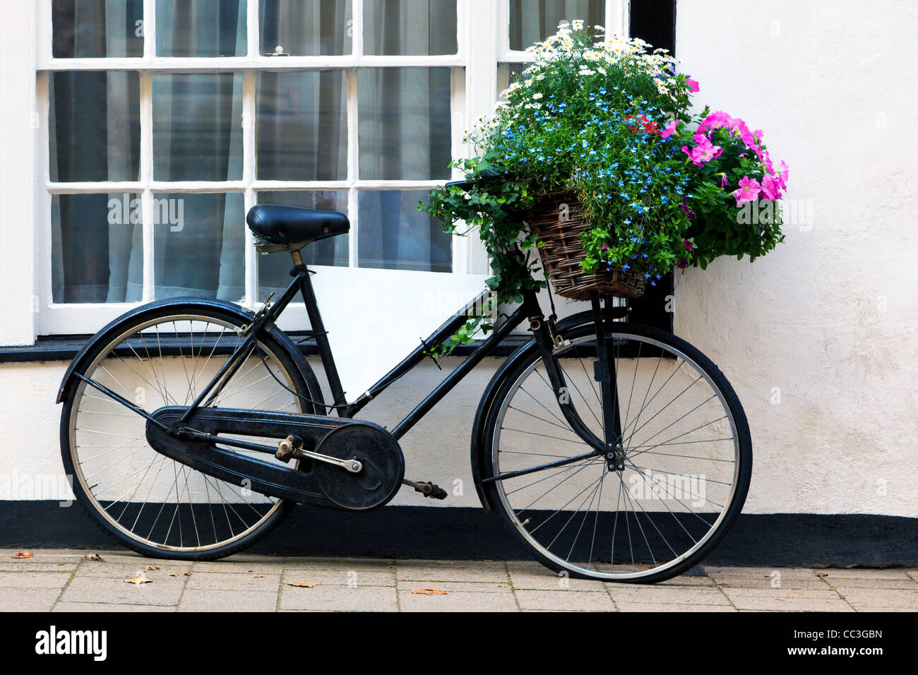 Photo of an old bicycle with a basket full of flowers and a blank advertising board in the frame. - Stock Image