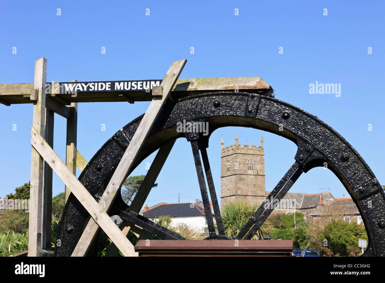 Zennor Cornwall England UK. Trewey Mill working water wheel outside Wayside Museum with village church of St Senara - Stock Image