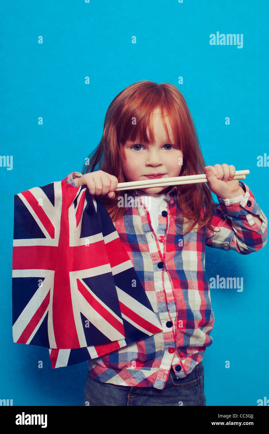 A young girl holding two British flags - Stock Image