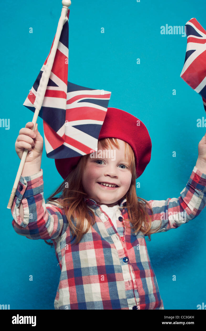 A young girl waving two British flags - Stock Image