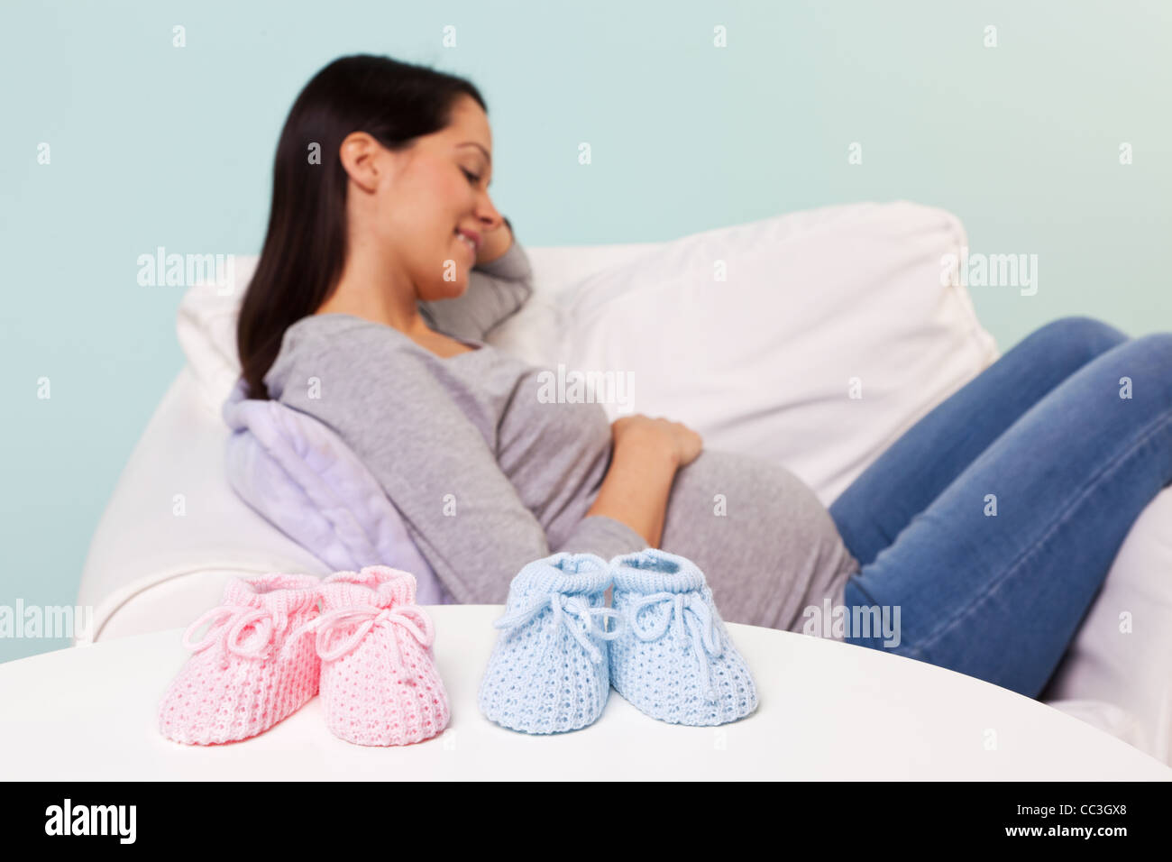 Photo of a pregnant woman at home sitting in an armchair with the focus on a pair of boy and girl knitted baby booties - Stock Image