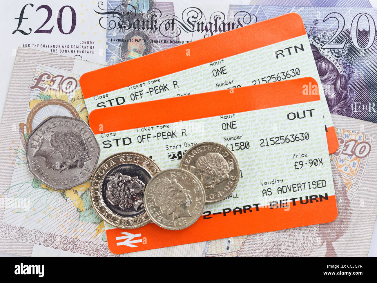 Two UK train tickets for Standard off-peak value travel out and return with sterling money banknotes and coins. - Stock Image
