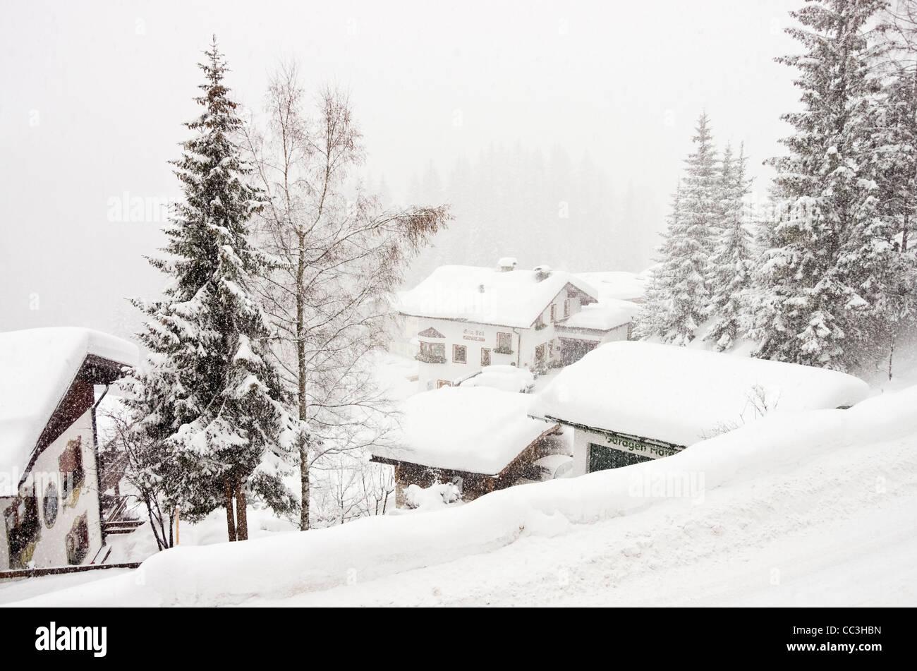 St Anton am Arlberg, Tyrol, Austria. Traditional Austrian village buildings during heavy snowfall in winter - Stock Image
