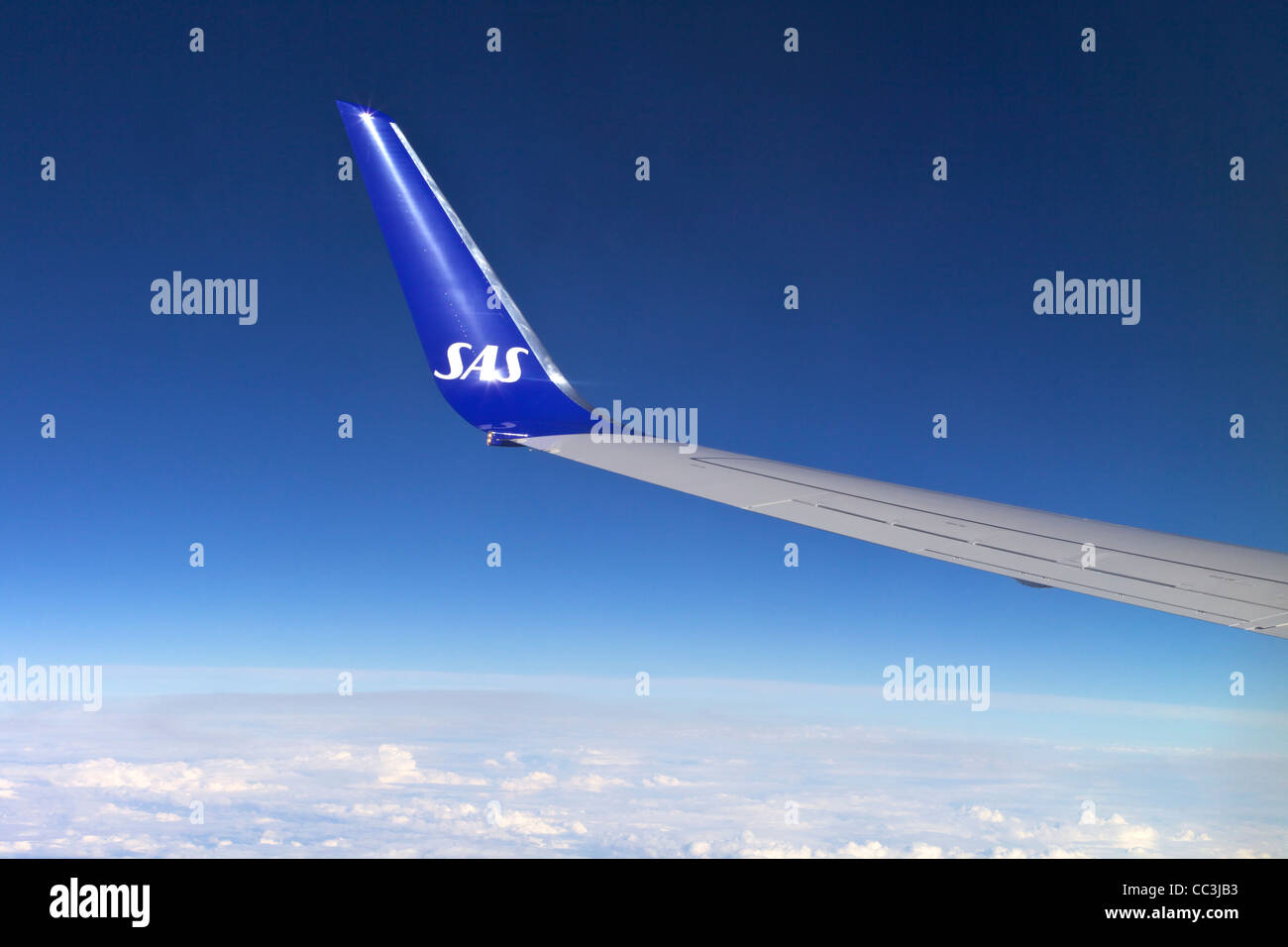 Scandinavian Air Services SAS wing from jet passenger window against polarised blue sky - Stock Image