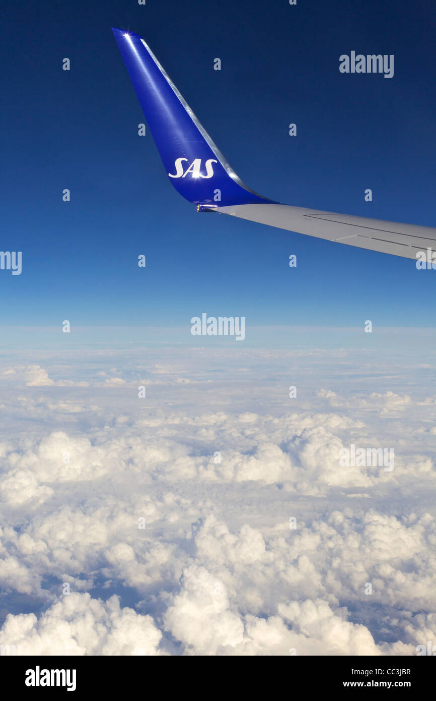 Scandinavian Air Services SAS wing, from jet passenger window, against polarised blue sky - Stock Image