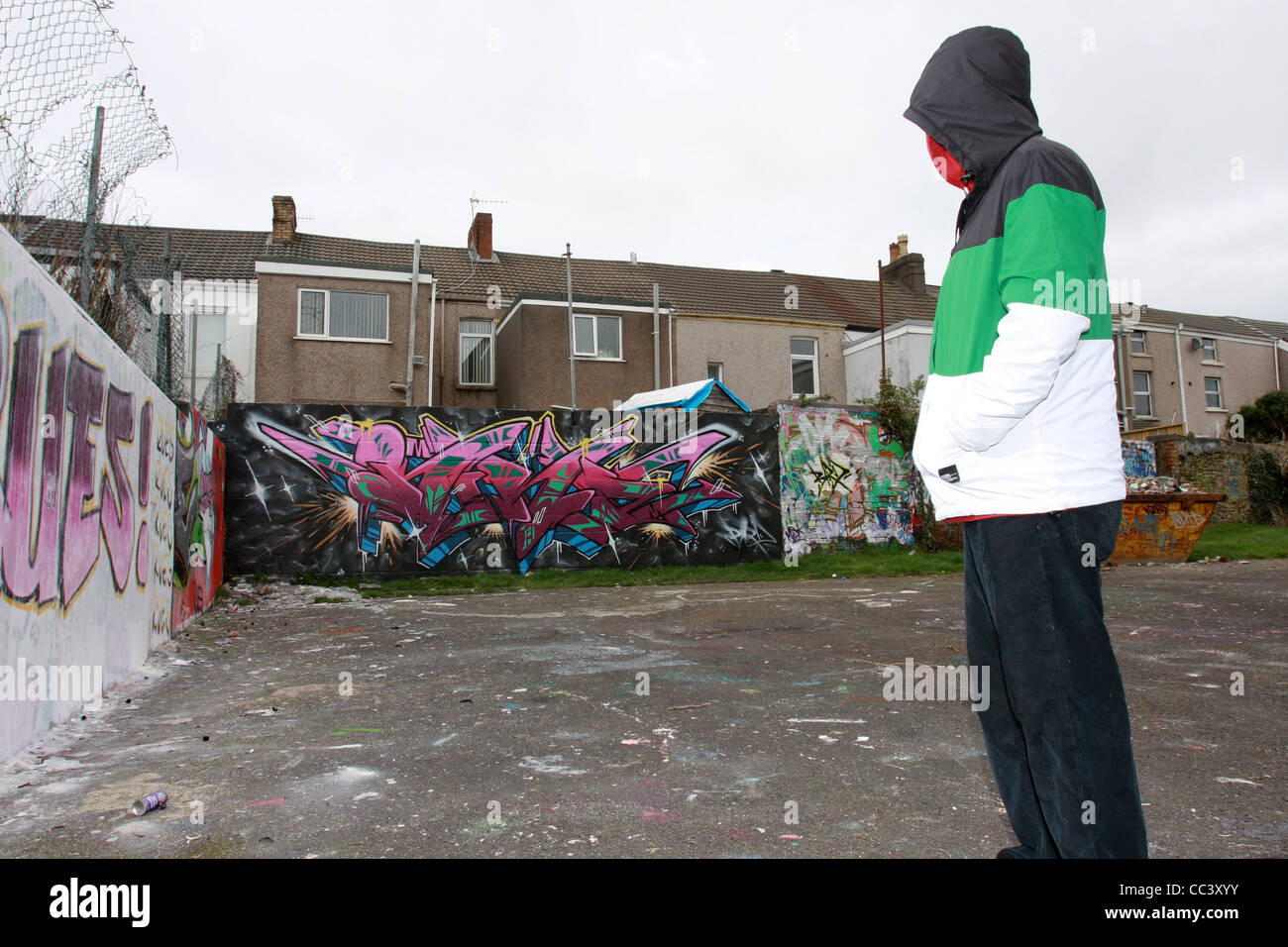 A Graffiti Writer Poses Anonymously Wearing A Hooded Jacket Inform Of One Of His Pieces A Large Scale Wall Mural