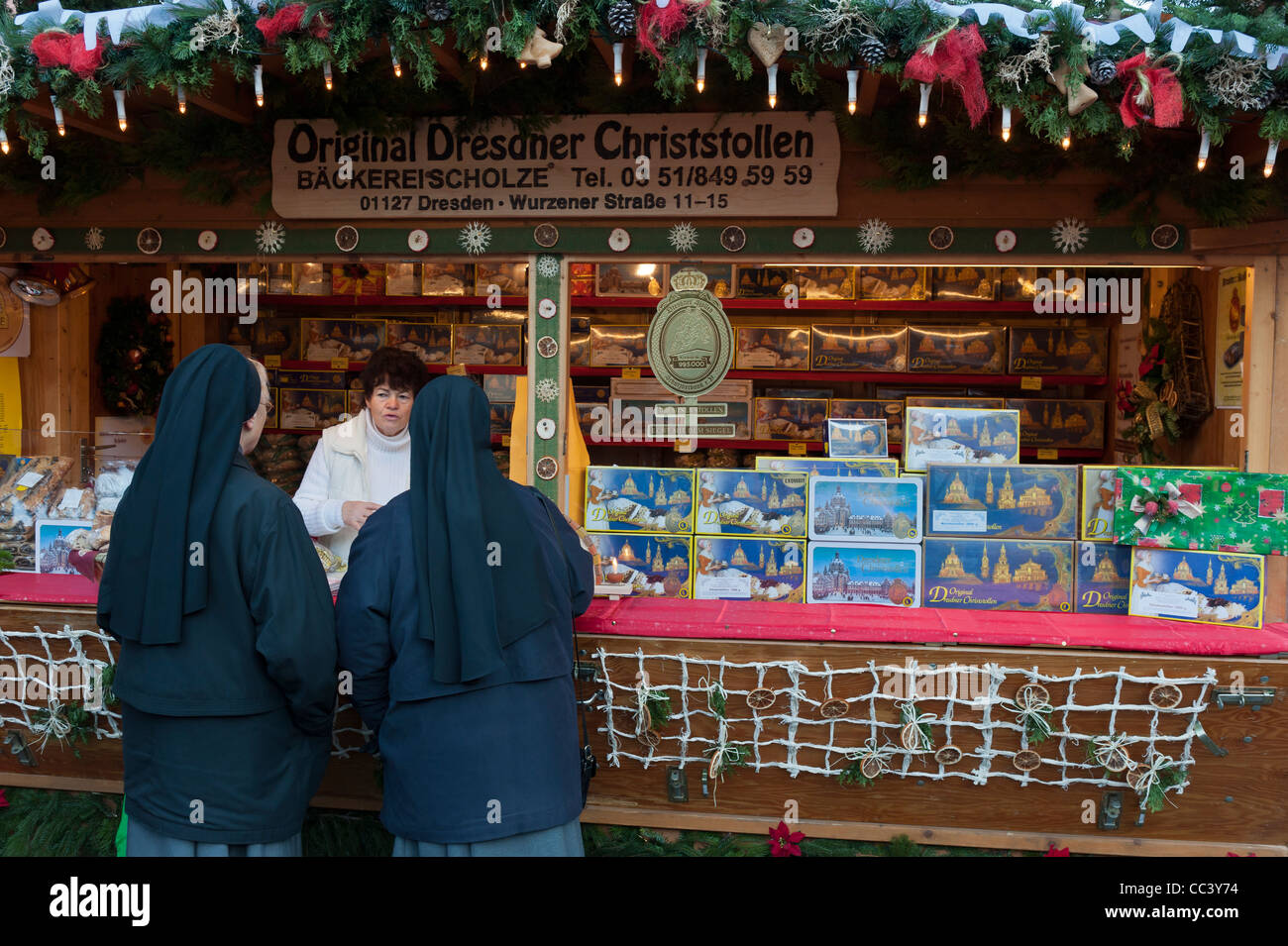 Two nuns at a Christmas Stollen cake stall. Stietzelmarkt Christmas market in Dresden. Saxony, Germany, Europe - Stock Image