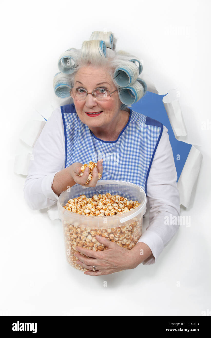 senior woman with curlers in her hair eating popcorn stock photo