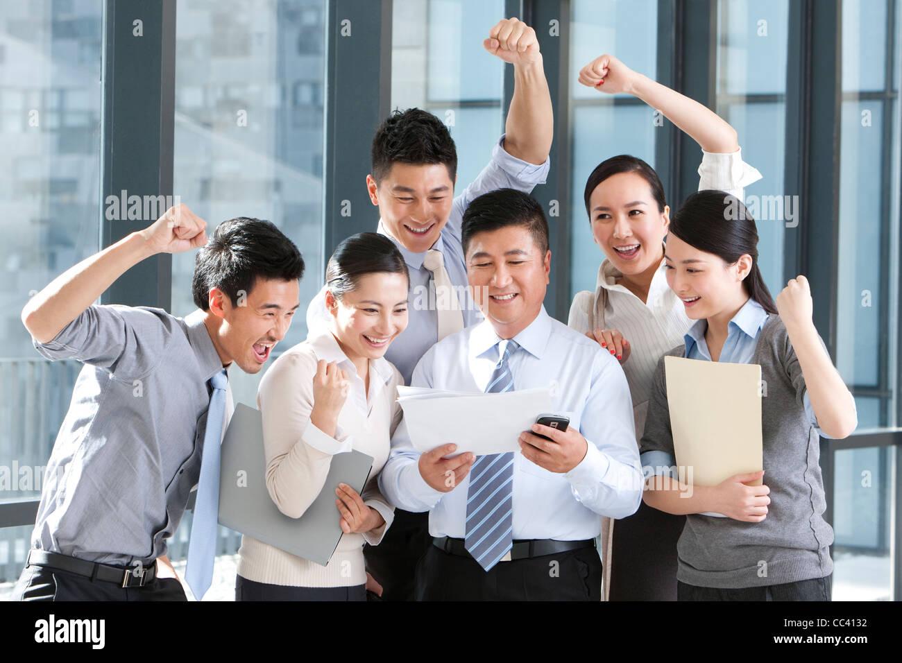 Businesspeople cheering over good news - Stock Image