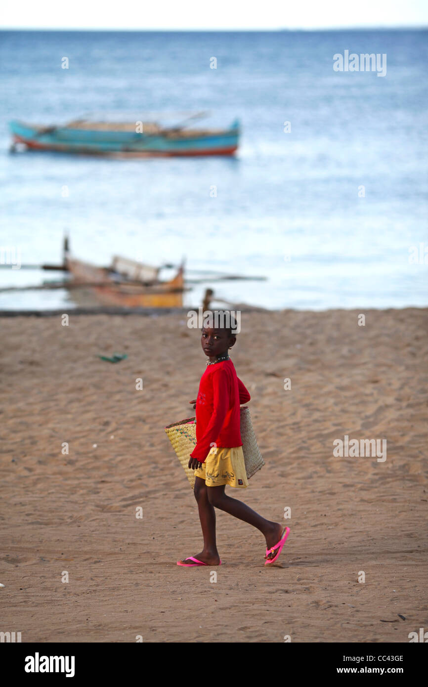 a2c0605334ec1 A young malagasy girls wearing pink flip flops and carrying a vime basket  walking at the
