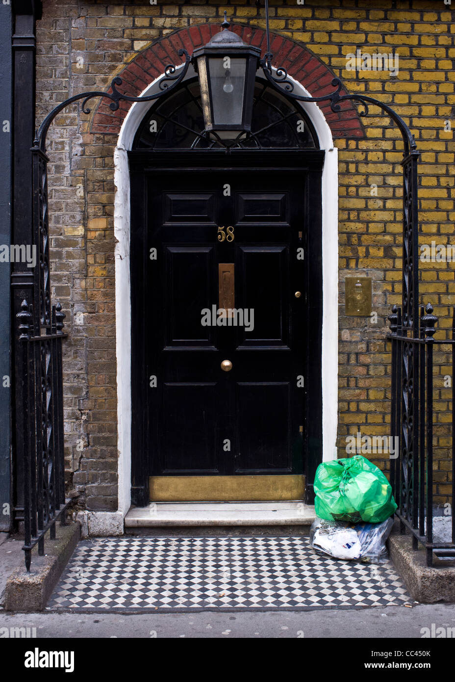Black front door with wrought iron archway and rubbish - Stock Image