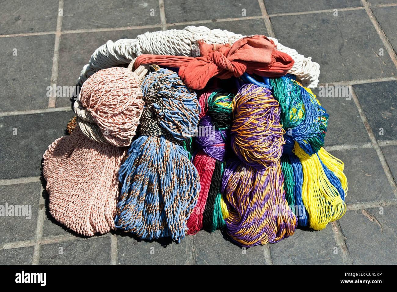 bundle of multicolored mesh hammocks sits on paving stones of Oaxaca Zocalo Mexico - Stock Image