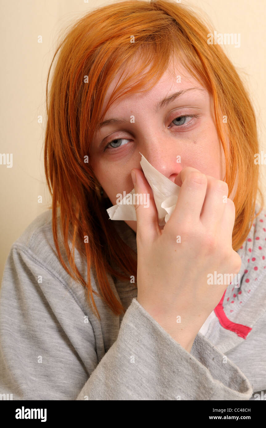 Young Women In  Unwell.Blowing Nose. - Stock Image