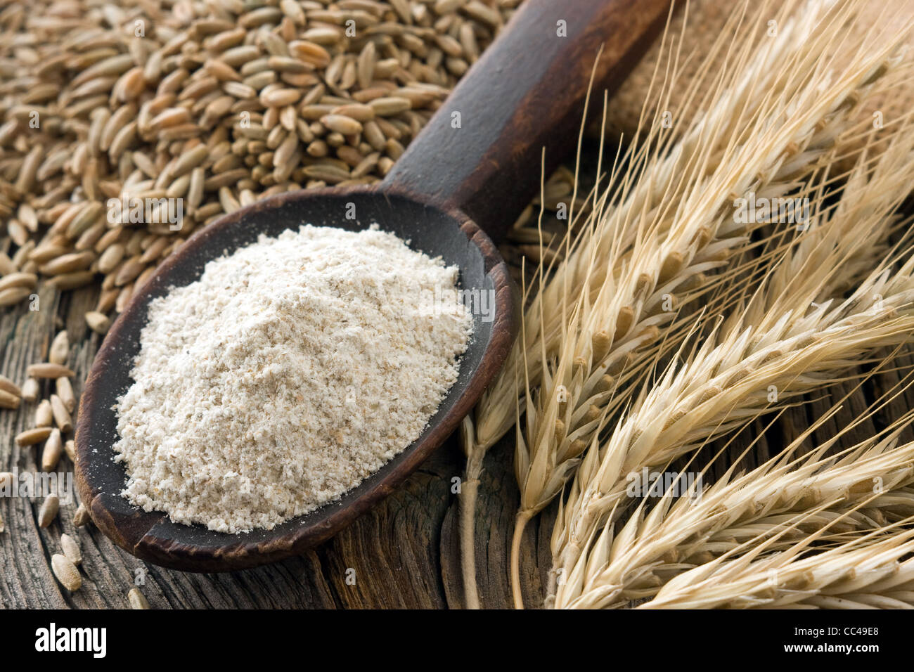 Flour whole-meal on old wooden spoon and rye ears - Stock Image