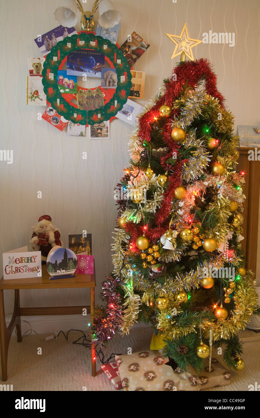 UK Christmas scene with decorated tree with lights and tinsel presents underneath and cards - Stock Image
