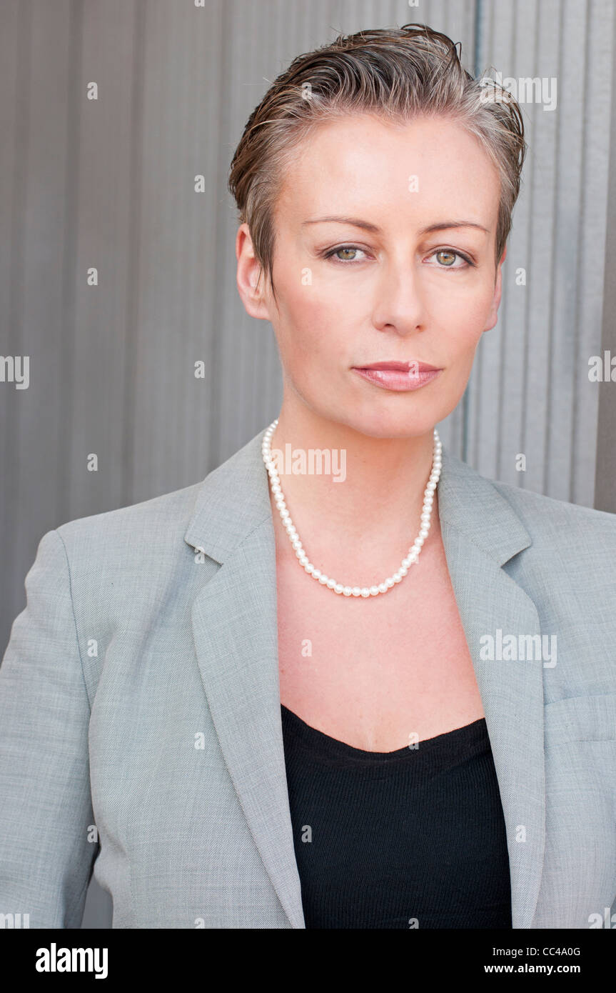 portrait of upscale business middle aged woman with short hair in gray suit. - Stock Image