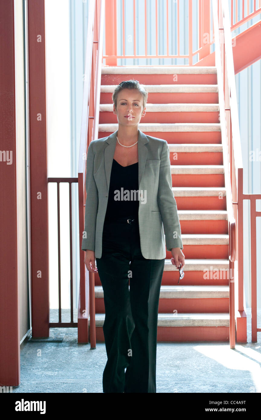 professional middle aged working woman walking to office near industrial stairs - Stock Image