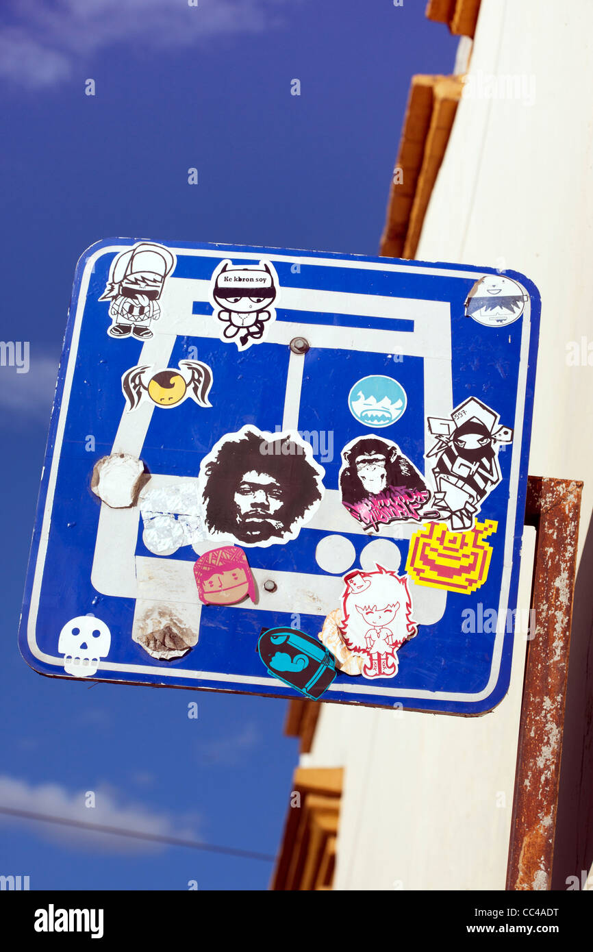 cheerfully defaced bus stop sign in Oaxaca Mexico - Stock Image