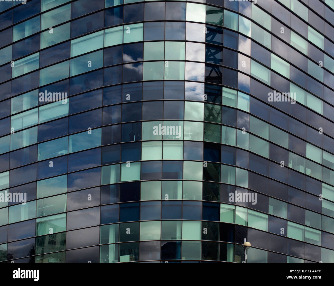 blue green mosaic glass frontage of curved futuristic building at Salford Quays,Manchester - Stock Image