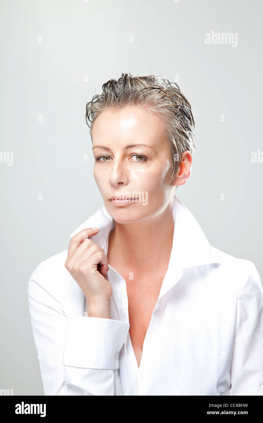 beautiful middle aged woman wearing white with low collar blouse looks at camera - Stock Image