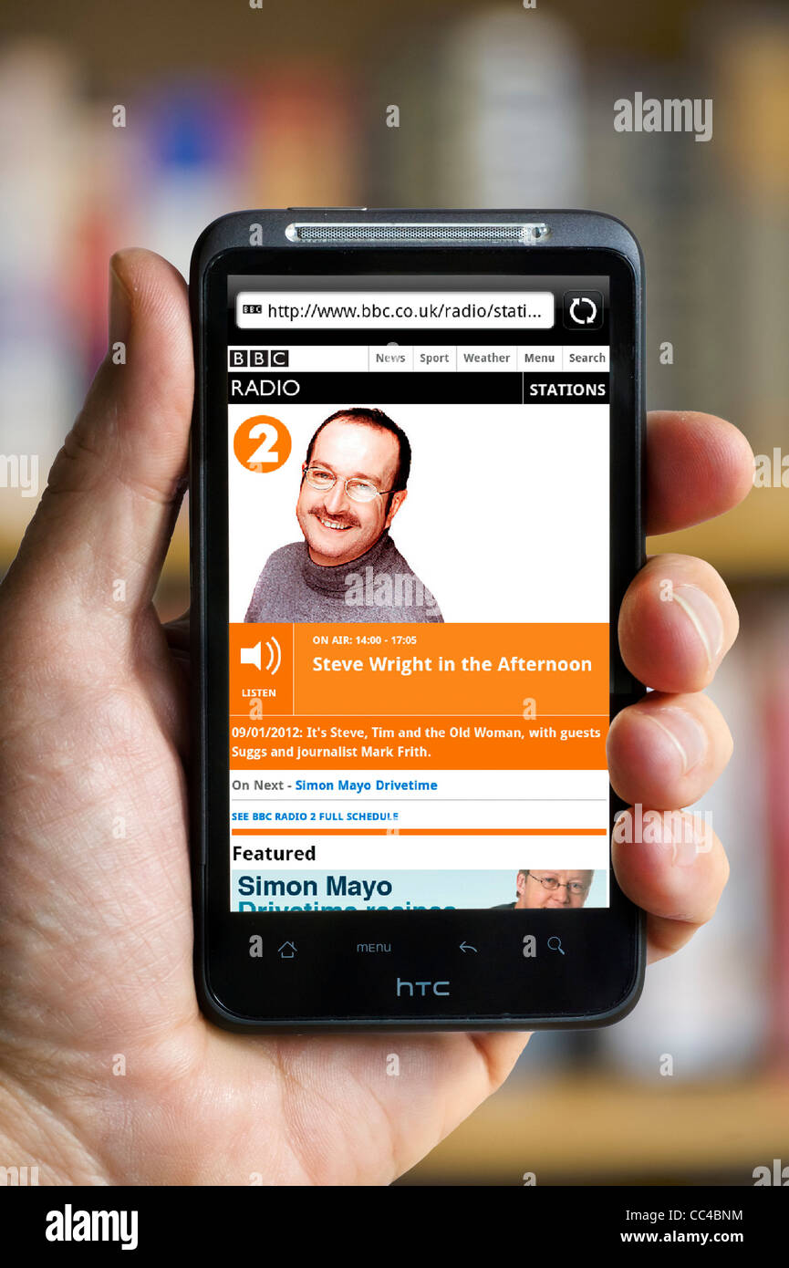 Listening to BBC Radio 2's Steve Wright in the Afternoon streaming on an HTC smartphone - Stock Image