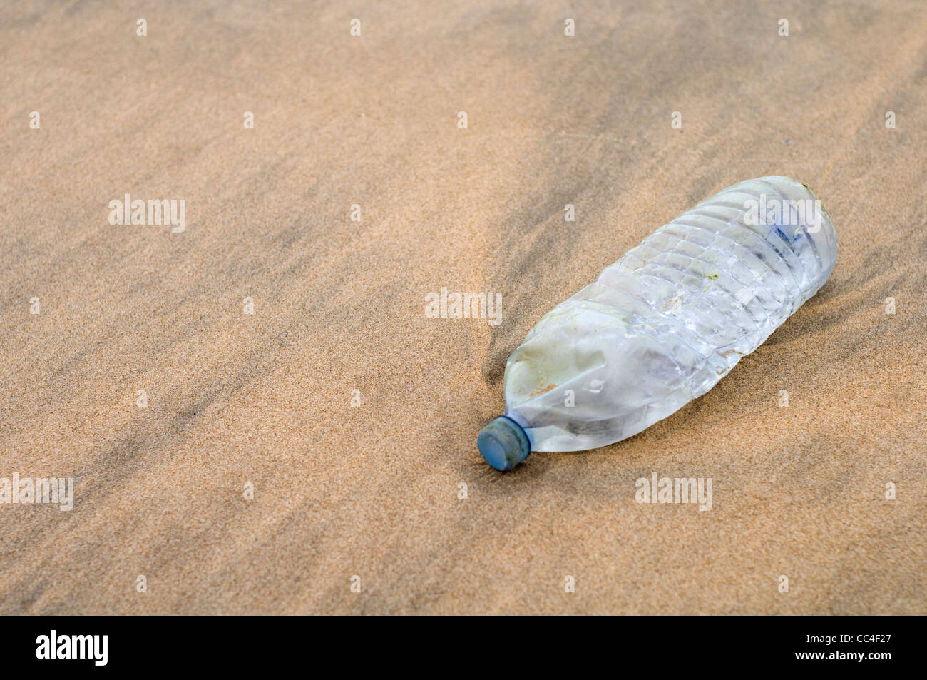 A plastic bottle polluting a sandy beach - Stock Image