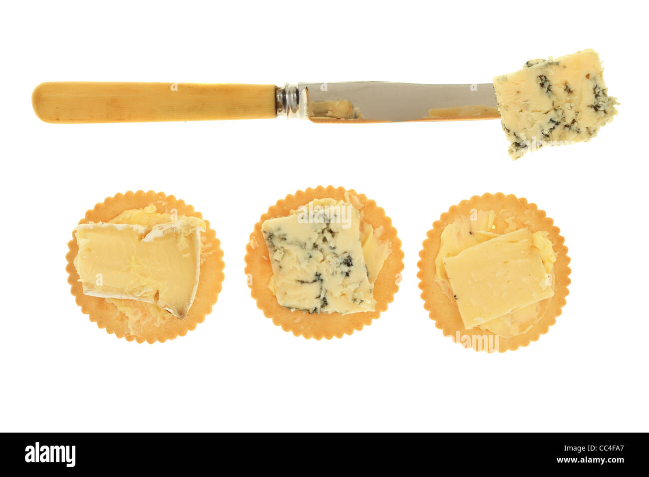 Cheese on biscuits with a knife isolated against white - Stock Image