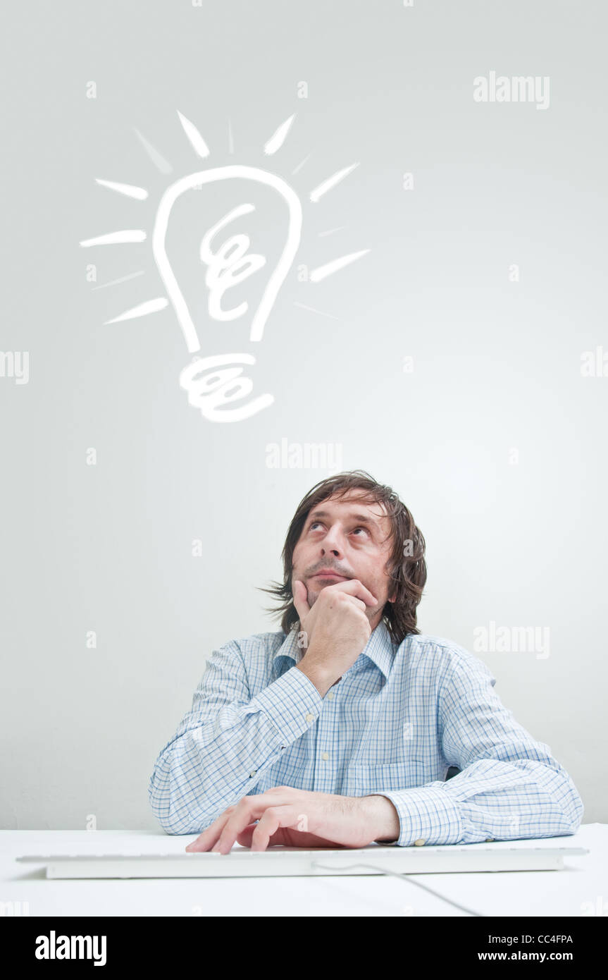 Businessman with an idea, drawn light bulb above his head - Stock Image