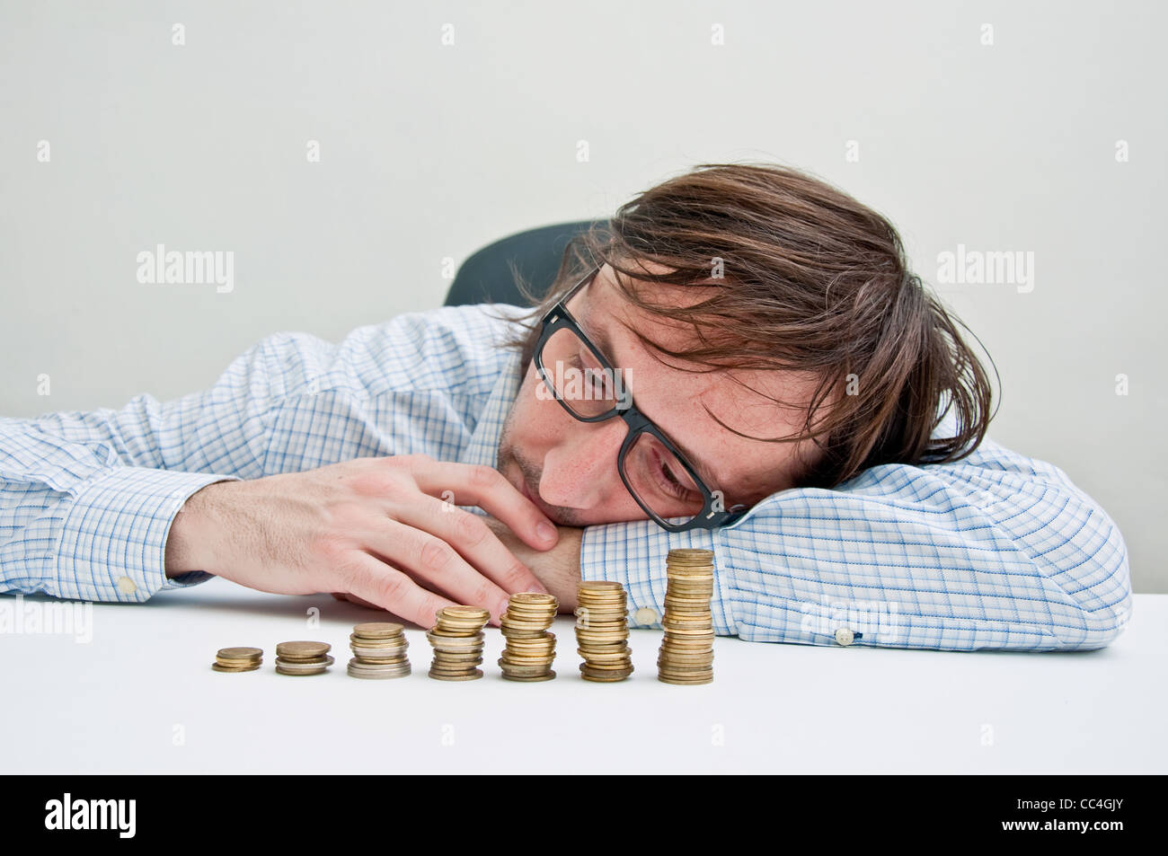 Businessman siting at the table and thinking about possible dollar investments. - Stock Image